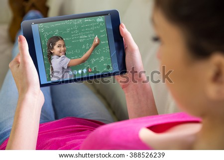 Woman using tablet at home against green - stock photo