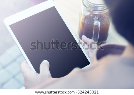 Woman using tablet computer and drinking coffee. Focus on tablet.