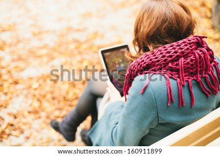 Woman using tablet computer sitting on park bench - stock photo