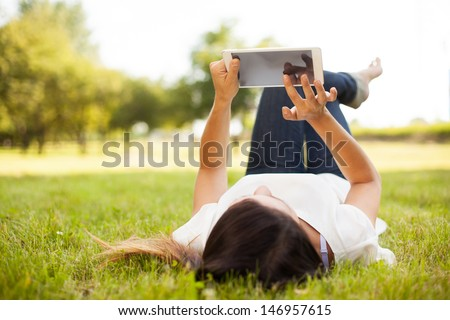 Woman using tablet outdoor laying on grass - stock photo