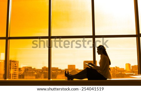 woman using tablet with sunbeams and lens flare Business girl young adult sit on windowsill against sunset sky window texture background Empty space for inscription Full length silhouette portrait  - stock photo