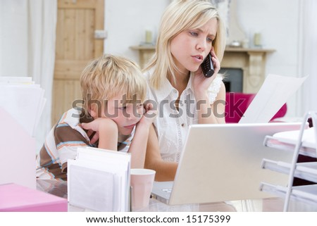 Woman using telephone in home office with laptop while young boy waits
