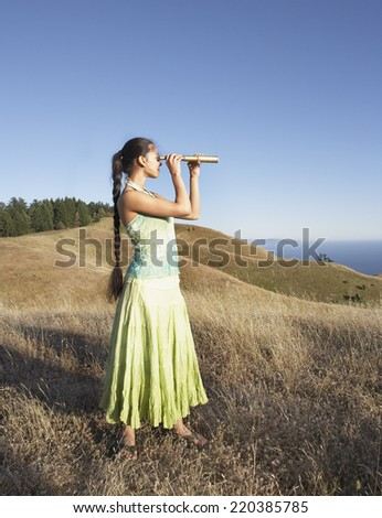 Woman using telescope to view distant hills - stock photo