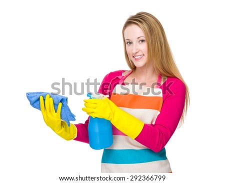 Woman using the bottle spray and rag for cleaning - stock photo