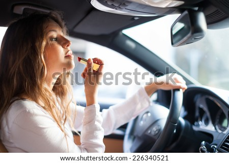 Woman using the rear-view mirror to apply make-up while driving her car - stock photo