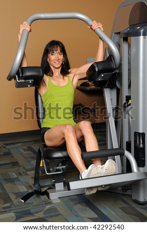 Woman using weight machine in a gym