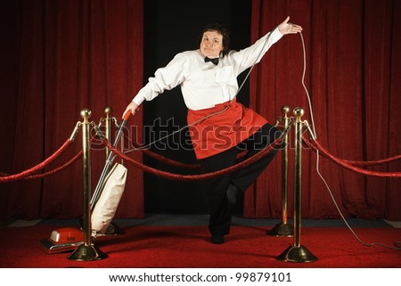 Woman vacuuming the red carpet - stock photo