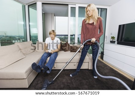 Woman vacuuming while man play video game in living room at home - stock photo