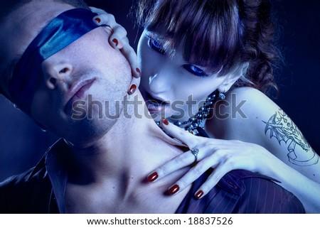 woman vampire bites a blind man - stock photo