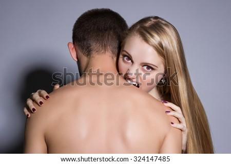 woman vampire bites a man's neck - stock photo
