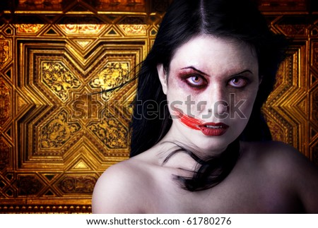 Woman vampire with blood in his mouth. Gothic Image halloween over gold background - stock photo