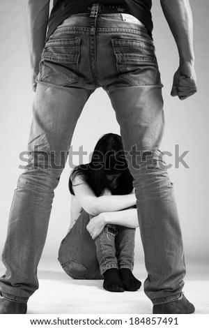 Woman victim of domestic violence and abuse. Husband intimidates his wife. Focus on woman - stock photo