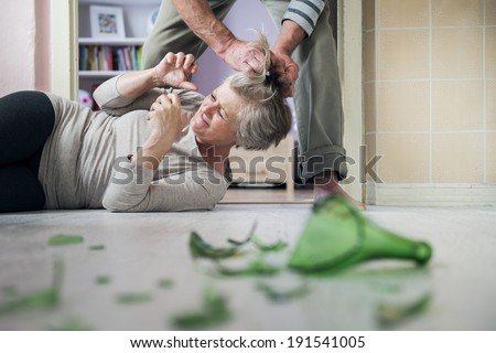 Woman victim of domestic violence and abuse. Mature woman scared of a man with broken bottle - stock photo