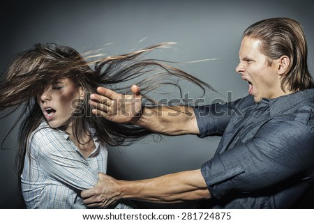 Woman victim of domestic violence and abuse. The quarrel in the family. A man beats a young woman - stock photo