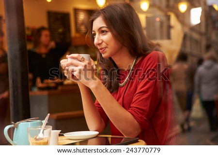 Woman Viewed Through Window Of Caf�¢?? Enjoying Cup Of Coffee - stock photo