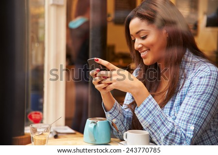 Woman Viewed Through Window Of Caf�¢?? Using Mobile Phone - stock photo