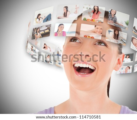 Woman viewing pictures around her head and smiling on grey background - stock photo