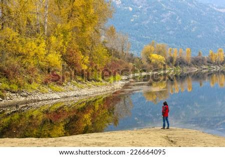 Woman views autumn landscape at the Kootenai River in autumn. - stock photo
