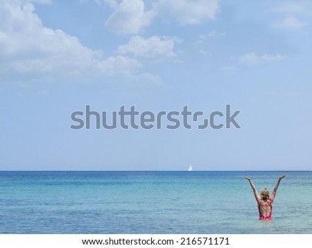 Woman wading in ocean with arms raised and sailboat in distance - stock photo