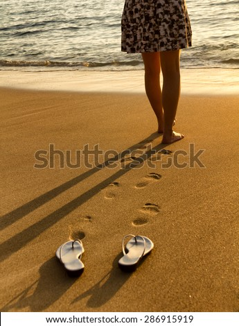 Woman, waist down, walking barefoot into Pacific Ocean during golden sunset. Focus on foot prints with sandals in forefront.  - stock photo