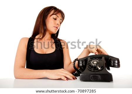 Woman waiting a call next to an old style phone - isolated over white - stock photo