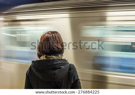 Woman Waiting at a Subway Station with a Train in Motion Pulling into the Platform - stock photo