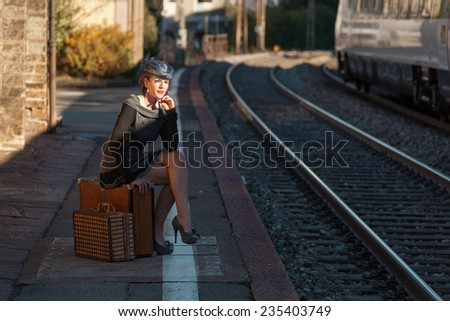 Woman waiting at the railway station - stock photo