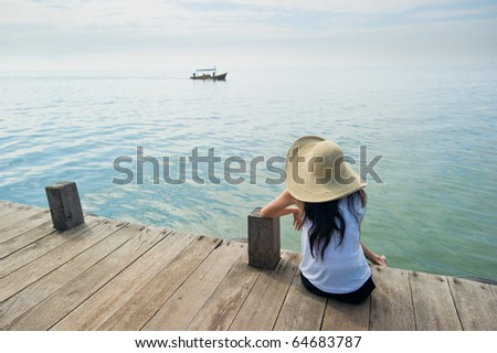 woman waiting for boat at the dock - stock photo