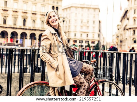 Woman waiting friends for a meeting, while she is sitting on her bicycle.  - stock photo