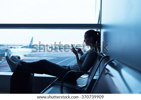 Woman waiting in airport terminal using her smartphone - stock photo
