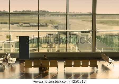 woman waiting in the airport at sunset - stock photo