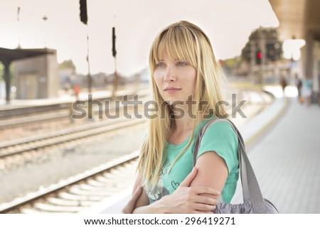 woman waiting on train station - stock photo