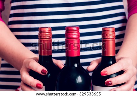 Woman waitress holding a bottle of wine for serving - stock photo