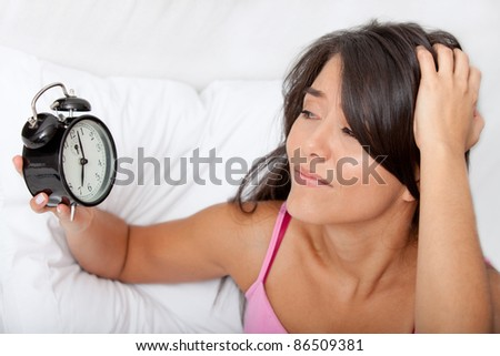 Woman waking up and running late looking at the alarm clock - stock photo