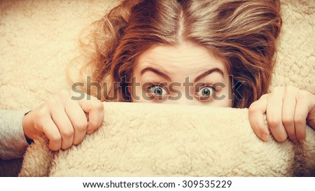 Woman waking up in bed in the morning after sleeping. Well rested young girl laying covering face with wool woolen blanket. Instagram filter. - stock photo