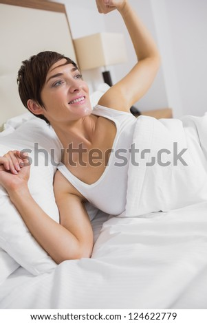 Woman waking up in hotel room - stock photo