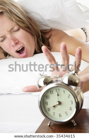 Woman waking up late and reaching for her alarm clock - stock photo