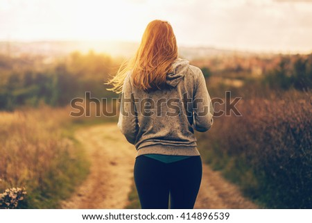 Woman walking a path down the hill - stock photo