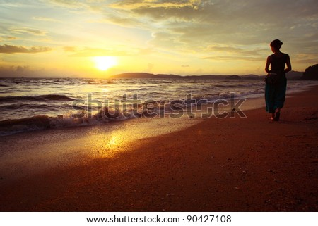 Woman walking alone on a sandy beach and looking to the sun - stock photo