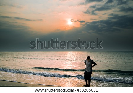 Woman walking alone on the seaside and watching the sunset or sunrise.