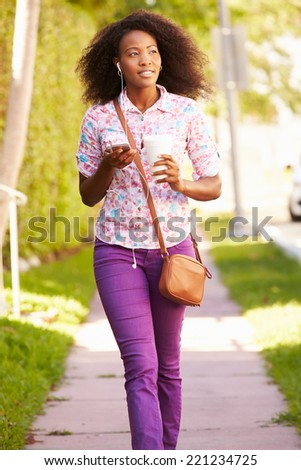 Woman Walking Along Street To Work Listening To Music - stock photo