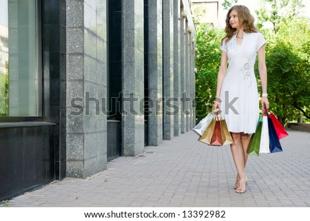 Woman walking along the shop windows with her bags - stock photo