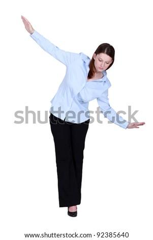 Woman walking an imaginary tightrope - stock photo