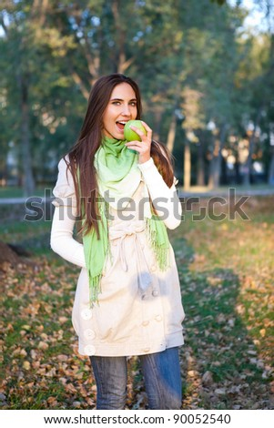 woman walking autumn park and eating apple