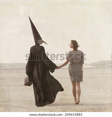 Woman walking away through the desert accompanied by the mysterious person in the plague mask, view from back - stock photo