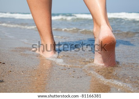 Woman walking barefoot on sunny beach in summer day - stock photo