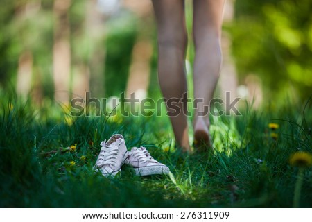 Woman walking barefoot on the green grass, shoes in focus, shallow DOF - stock photo