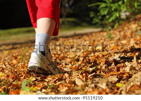 Woman walking cross country and trail in autumn forest - stock photo