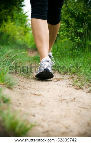 Woman walking cross country and trail in forest - stock photo