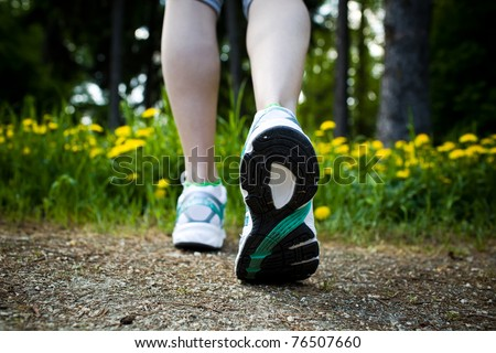 Woman walking cross country and trail in spring forest